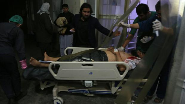 A man injured in a suicide bombing is brought into a hospital for treatment, (Rahmat Gul/AP)