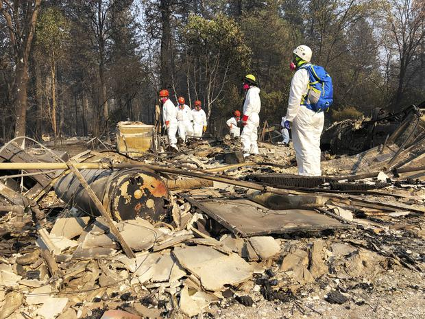 Volunteers search the ruins of a home in Paradise, California (Sudhin Thanawala/AP)