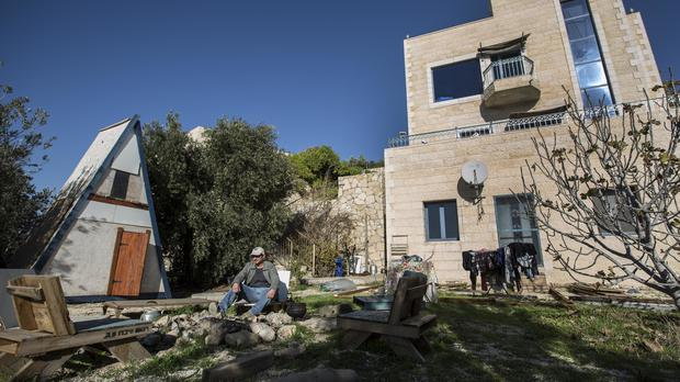 Moshe Gordon sits outside his guest house in the West Bank (AP Photo/Tsafrir Abayov, File)