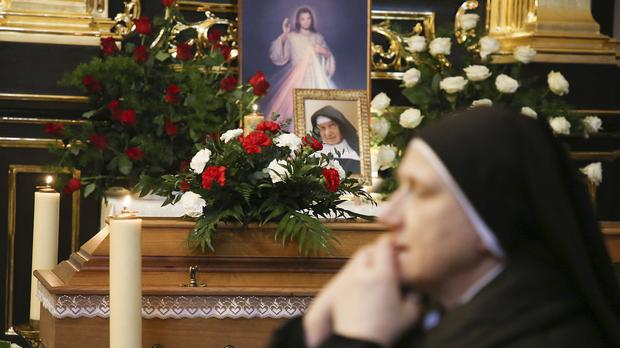 A nun prays beside the coffin and photo of 110-year-old Roman Catholic Sister Cecylia Roszak, believed to be the world's oldest nun, and a rescuer of Jews during the Holocaust (Beata Zawrzel/AP)