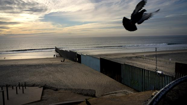 A pigeon flies near where the border structure that separates Mexico from the US (Ramon Espinosa/AP)