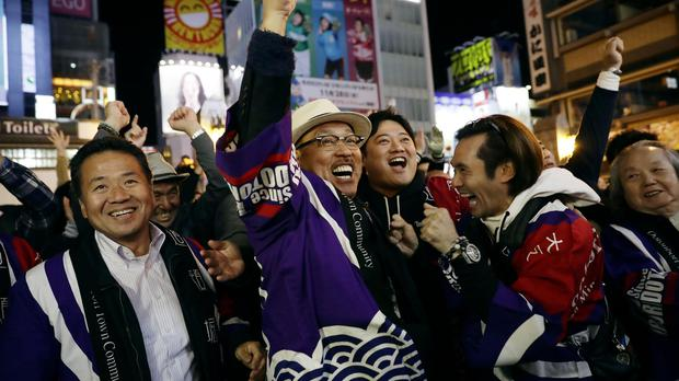 People in Osaka celebrate (Kyodo News via AP)