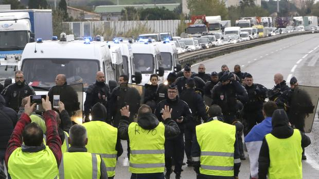 Protesters dubbed the 'yellow Jackets' face riot police as they block a crossroads in southern France in protest against rising fuel and oil prices (Claude Paris/AP)