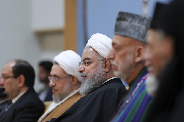 Iranian President Hassan Rouhani, centre, at the annual Islamic Unity Conference in Tehran (Iranian Presidency Office/AP)
