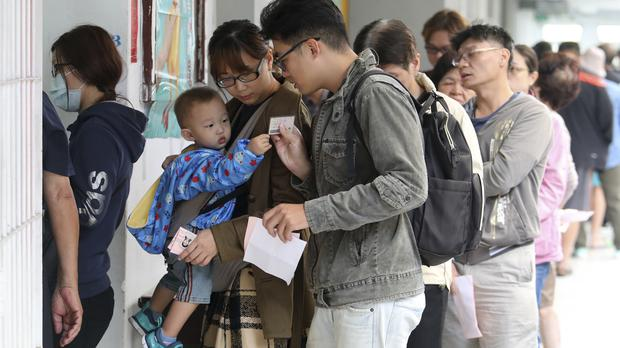 Voters line up at a ballot station to vote for the city mayor in Kaohsiung (AP)