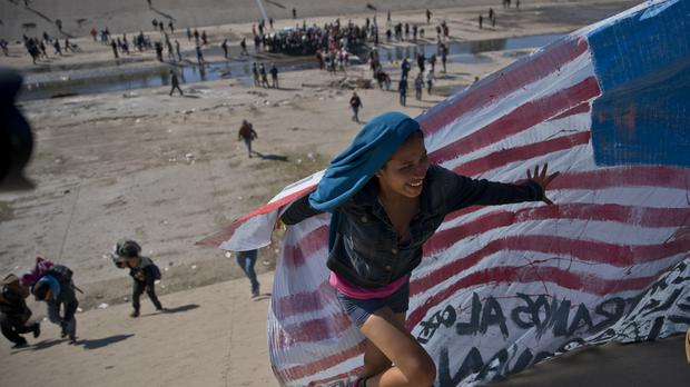 Migrants cross a riverbed at the Mexico-U.S. border (Ramon Espinosa/AP)
