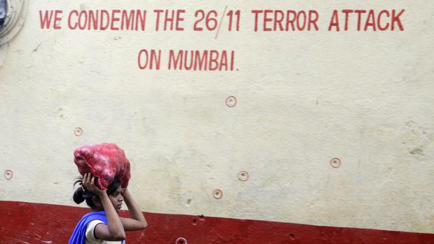 A girl walks past a bullet-marked wall of the Chabad House in Mumbai (Rajanish Kakade/AP)