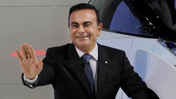 Carlos Ghosn poses with an electric vehicle at the Tokyo Motor Show (Itsuo Inouye/AP)