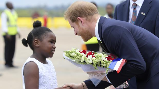 The Duke of Sussex receives flowers from a girl upon his arrival at Kenneth Kaunda airport in Lusaka (Tsvangirayi Mukwazhi/AP)