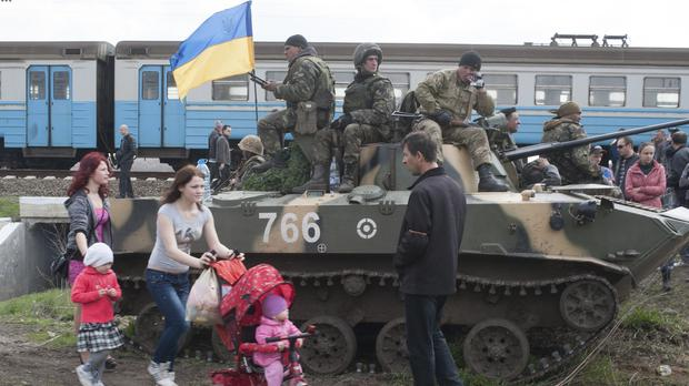 People walk past a Ukrainian army combat vehicle parked near a railway in Kramatorsk, Ukraine, in 2014 (Evgeniy Maloletka/AP)