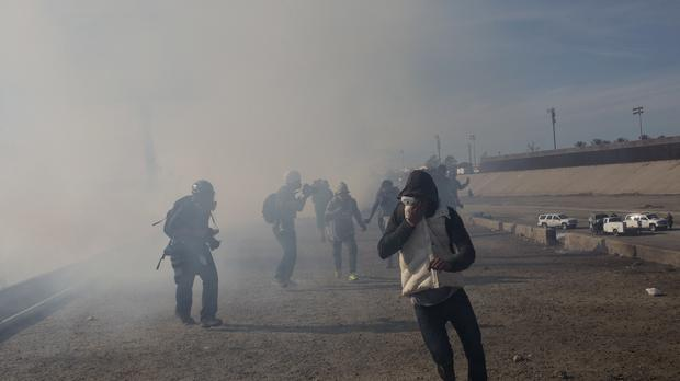 Migrants run from tear gas launched by US agents (Rodrigo Abd/AP)