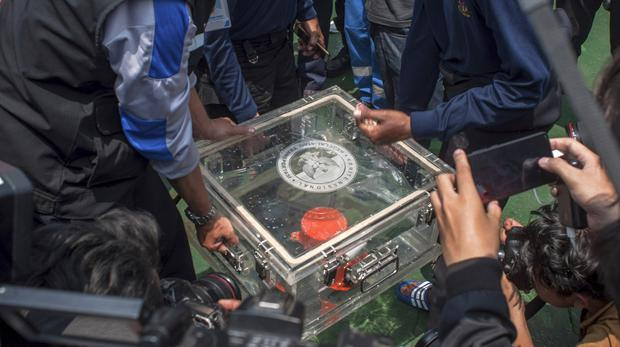 Members of the National Transportation Safety Committee lift a box containing the flight data recorder from a crashed Lion Air jet (AP Photo/Fauzy Chaniago, File)
