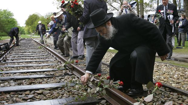 A Rabbi puts a rose on the tracks at Westerbork in the Netherlands (Peter Dejong/AP)