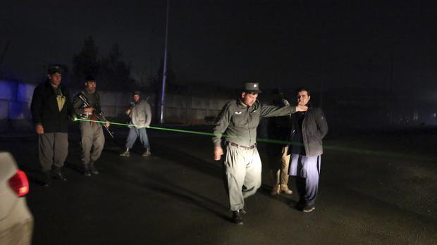 Security forces block the roads at the site of a suicide bomber attack (Rahmat Gul/AP)