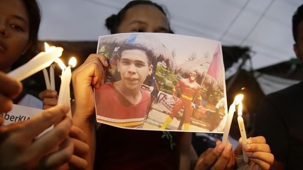 Activists light candles in front of the picture of 17-year-old student Kian Loyd delos Santos in Caloocan, metropolitan Manila (Aaron Favila/AP)