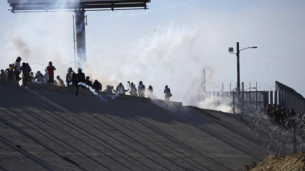 Migrants in Mexico stand amid tear gas (Ramon Espinosa/AP)