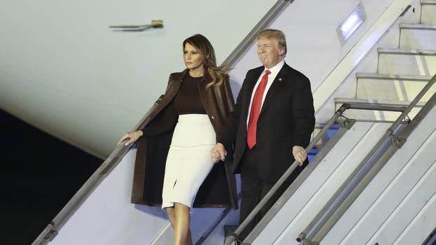 President Donald Trump and first lady Melania Trump walk from Air Force One (Martin Mejia/AP)