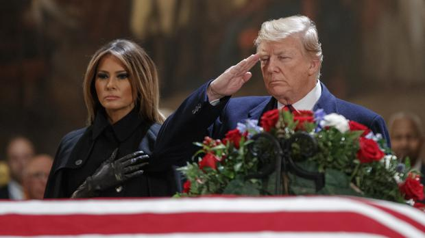 President Donald Trump salutes as he and first lady Melania Trump pay their respects to George HW Bush (Shawn Thew/Pool via AP)