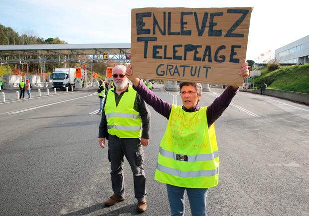 In action: A demonstrator holds a placard announcing free tolls after they opened the gates on a motorway near Biarritz, south-west France, yesterday. AP Photo/Bob Edme