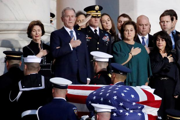 Ex-president George W Bush and other family members watch as the casket is carried by a joint services military honour guard to lie in state. Photo: REUTERS