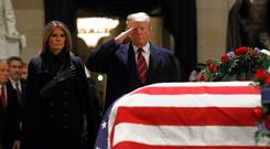 Lying in state: Donald Trump and wife Melania in front of the flag-draped casket of former president George HW Bush in the Capitol Rotunda in Washington. AP Photo/Patrick Semansky