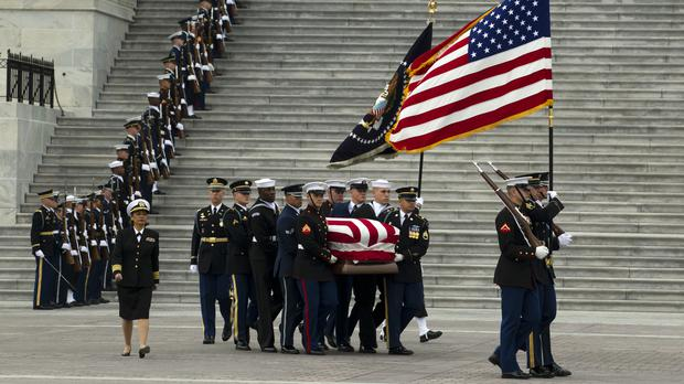 The flag-draped coffin of former President George H. W. Bush is carried by a joint services military honour guard (AP Photo/Jose Luis Magana)