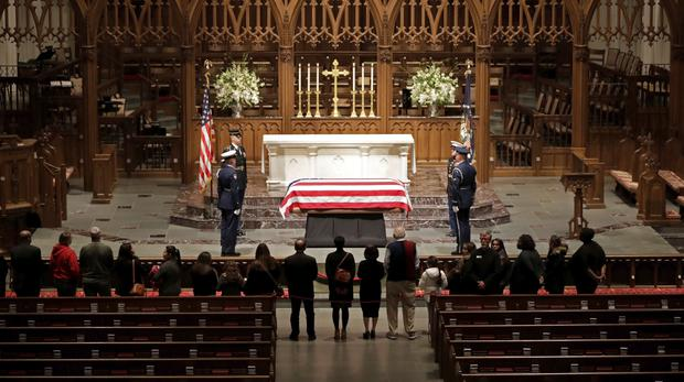 Visitors pay their respects to the flag-draped casket of former president George HW Bush at St Martin's Episcopal Church in Houston (Mark Humphrey/AP)