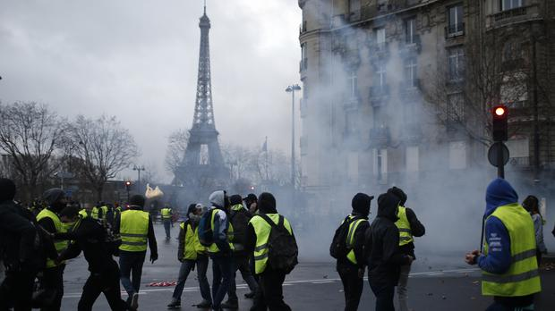 Demonstrators walk through tear gas during clashes Saturday, Dec. 8, 2018 in Paris. Crowds of yellow-vested protesters angry at President Emmanuel Macron and France's high taxes tried to converge on the presidential palace Saturday, some scuffling with police firing tear gas, amid exceptional security measures aimed at preventing a repeat of last week's rioting (Rafael Yaghobzadeh/AP)