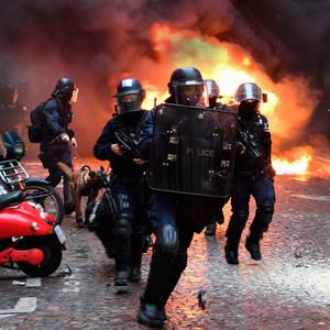 HIJACKED: Riot police run next to a car set on fire during yesterday's protests in Paris. Photo: Eric Feferberg/Getty