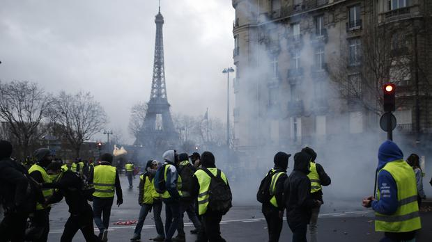 Demonstrators walk through tear gas during clashes Saturday, Dec. 8, 2018 in Paris. Crowds of yellow-vested protesters angry at President Emmanuel Macron and France's high taxes tried to converge on the presidential palace Saturday, some scuffling with police firing tear gas, amid exceptional security measures aimed at preventing a repeat of last week's rioting. (AP Photo/Rafael Yaghobzadeh)