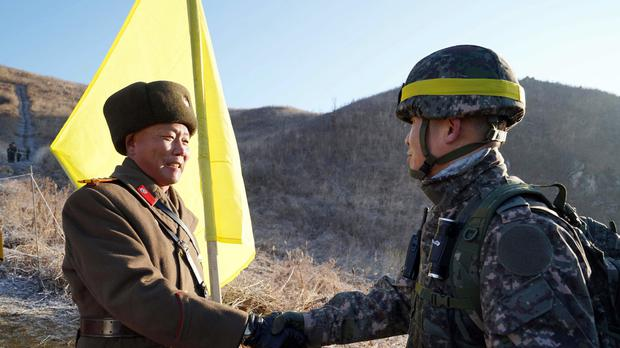 A South Korean soldier shakes hands with a North Korean rival (AP)