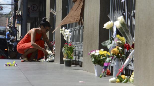 A woman leaves flowers at a makeshift memorial outside the Metropolitan Cathedral (Rovena Rosa/AP)
