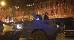 An armoured vehicle drives down the Champs-Elysees after clashes on December 8 (Rafael Yaghobzadeh/AP)