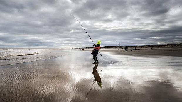 An angler on Tunstall Beach in Yorkshire (PA)