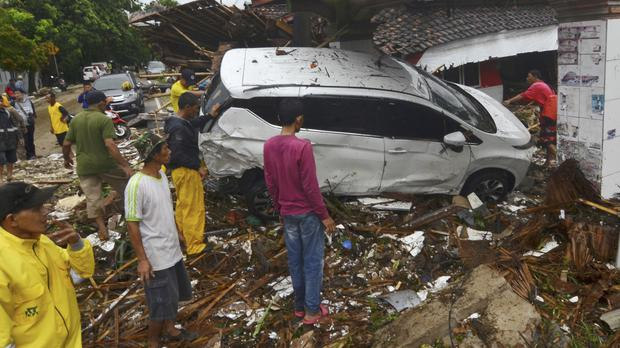 People inspect the wreckage of a car swept away by a tsunami in Carita, Indonesia (AP)