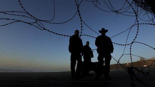 Border patrol officers stand at the beach on the US side of the fence between San Diego and Tijuana, Mexico (Daniel Ochoa de Olza/AP)