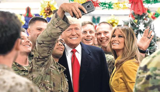 Surprise: US President Donald Trump and First Lady Melania Trump greet military personnel during an unannounced visit to Al Asad Air Base, Iraq. Photo: Jonathan Ernst/Reuters