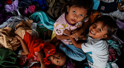 Danger: Children play on donated clothing after being evacuated following the December 22 tsunami that hit the west coast of Indonesia's Java island. Photo: Getty