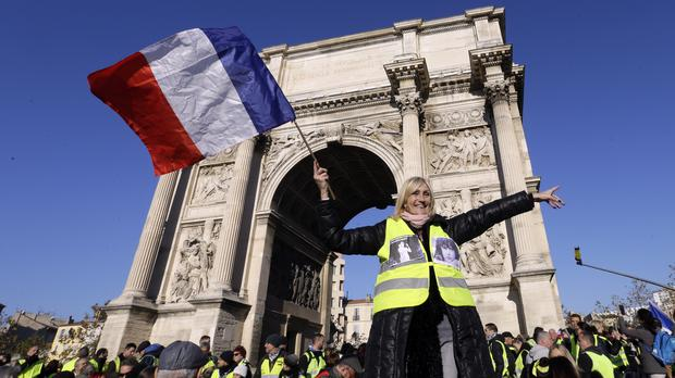 A demonstrator wearing her yellow vest waves a national flag (AP)