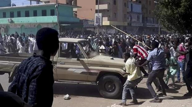 Protesters attack a national security vehicle during a protest in Kordofan (AP)