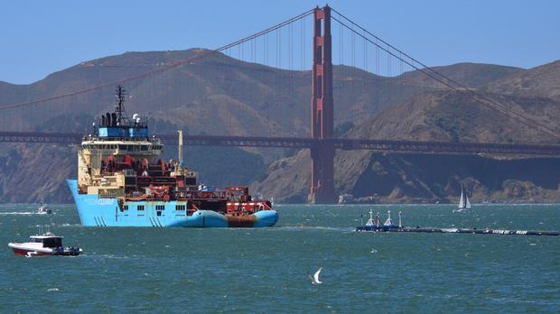 A ship tows The Ocean Cleanup's first buoyant rubbish-collecting device toward the Golden Gate Bridge in San Francisco en route to the Pacific Ocean (Lorin Eleni Gill/AP)