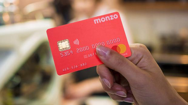 Monzo, known for its coral pink bank cards, is to create more than 300 jobs in Cardiff (Monzo/PA)