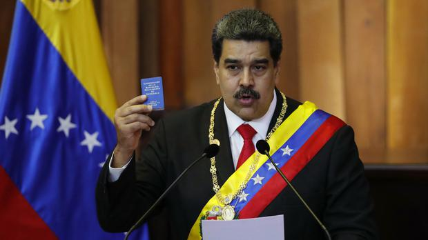 Venezuela's President Nicolas Maduro holds up a small copy of the constitution as he speaks during his swearing-in ceremony at the Supreme Court (Ariana Cubillos/AP)