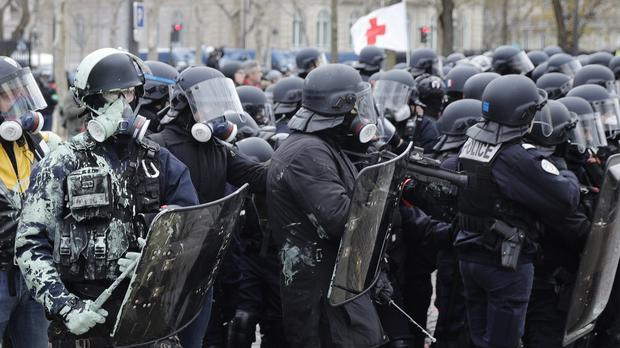 Riot police take up position during clashes with yellow vest protesters in Paris (Kamil Zihnioglu/AP)