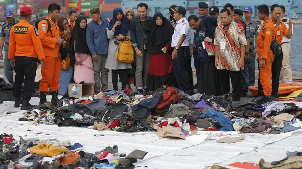 Relatives stand before belongings retrieved after the crash A