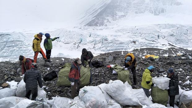 People collect rubbish at the north slope of Mount Everest (Awang Zhaxi/Xinhua via AP)