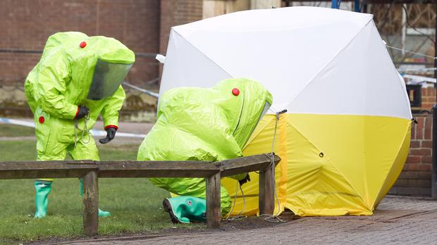 Personnel in hazmat suits securing a tent covering a bench in the Maltings shopping centre in Salisbury (Andrew Matthews/PA)