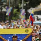 An opposition member holds a Venezuelan national flag during a protest march against President Nicolas Maduro in Caracas (Fernando Llano/AP)