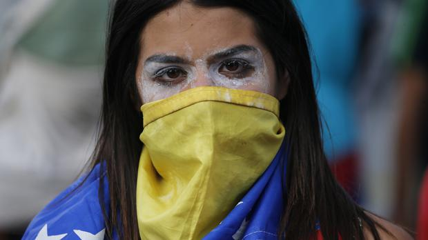 An anti-government protester covers her face with a Venezuelan flag (Fernando Llano/AP)