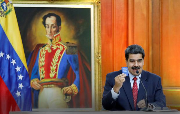 Venezuelan President Nicolas Maduro holds up a miniature version of his nation's constitution during a press conference at the presidential palace in Caracas